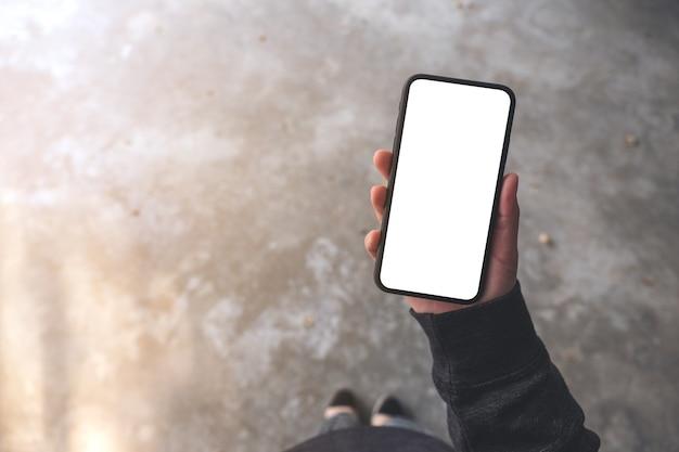 Вид сверху макета женщины, держащей черный мобильный телефон с пустым экраном рабочего стола, стоя на бетонном полу Premium Фотографии