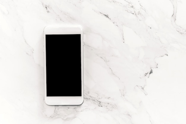 Top view of mockup smartphone with blank screens on white marble background. Premium Photo