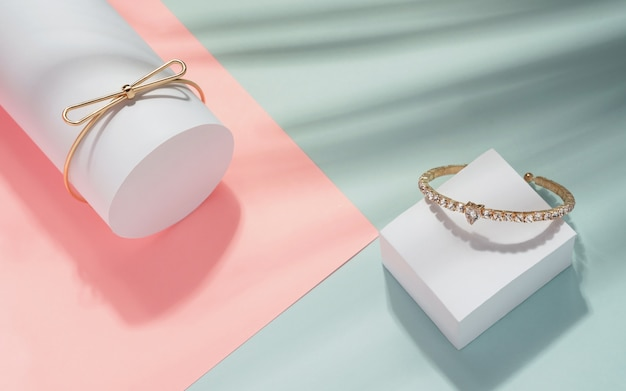 Top view of modern golden bracelets on geometric pastel colors background with tropical leaves shadow Premium Photo