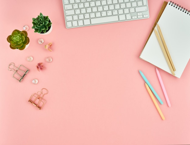 Top view of modern pink woman office desktop with blank notepad Premium Photo
