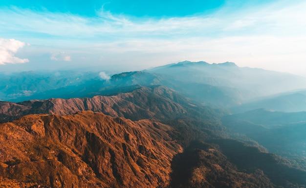 平面図朝の太陽とミャンマー、ムレイット山に覆われた霧の黄金の光 Premium写真