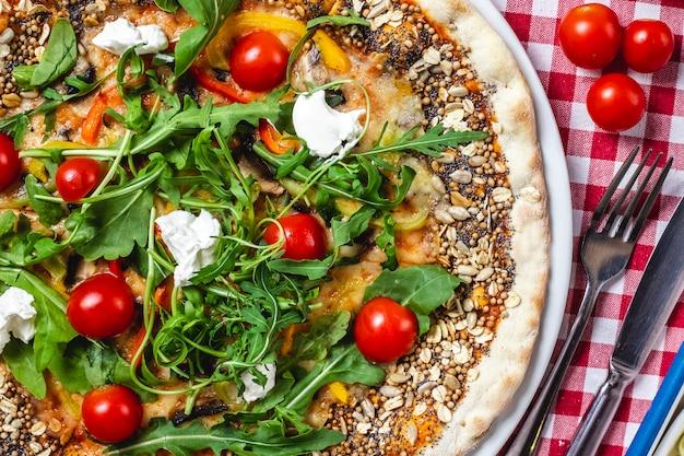 Вид сверху мультизерновая пицца со свежими помидорами черри, сыром моцарелла, сладким перцем и рукколой сверху Бесплатные Фотографии