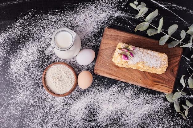 Vista dall'alto della torta napoleone accanto a uova, farina e latte su sfondo nero. Foto Gratuite
