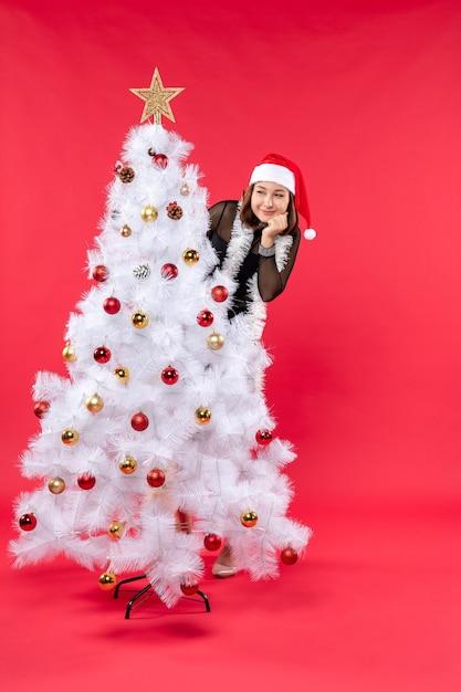 Vista dall'alto dell'umore del nuovo anno con una bella ragazza felice in un vestito nero con il cappello di babbo natale nascosto Foto Gratuite