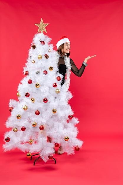 Vista dall'alto dell'umore del nuovo anno con sorridente bella ragazza in un abito nero con il cappello di babbo natale nascosto Foto Gratuite