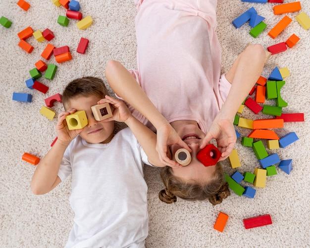 Vista dall'alto bambini non binari che giocano con un gioco colorato Foto Gratuite