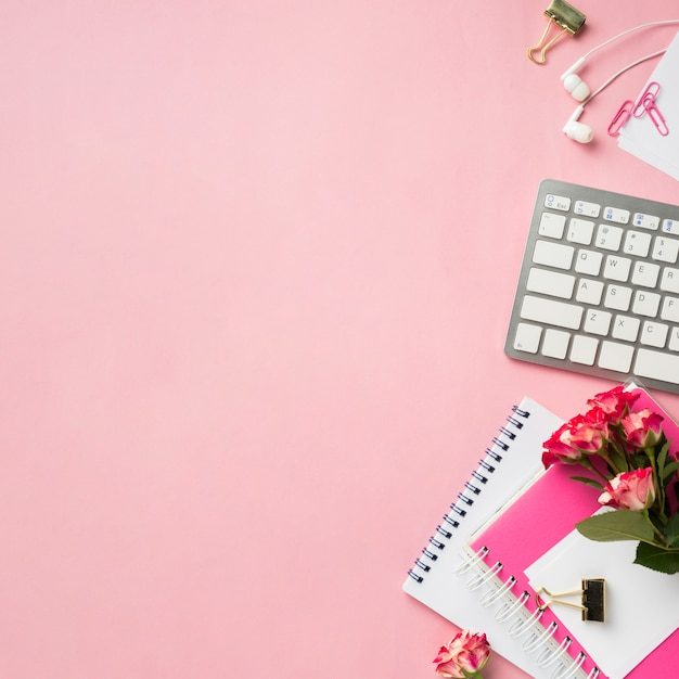 Top view of notebook and bouquet of roses on desk with copy space Free Photo