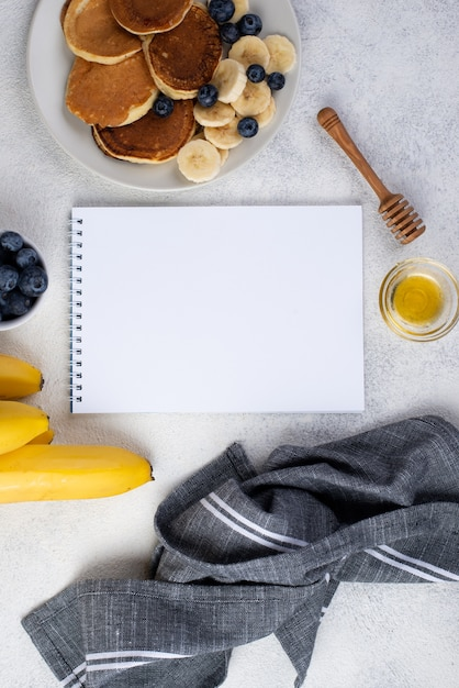 Top view of notebook and breakfast pancakes with banana slices and blueberries Free Photo