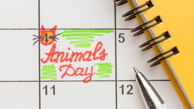 Top view of notebook and calendar for animal day Free Photo