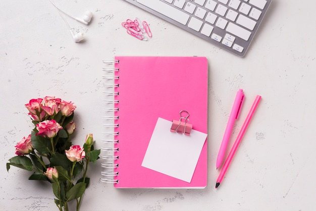Top view of notebook on desk with bouquet of roses and pens Free Photo