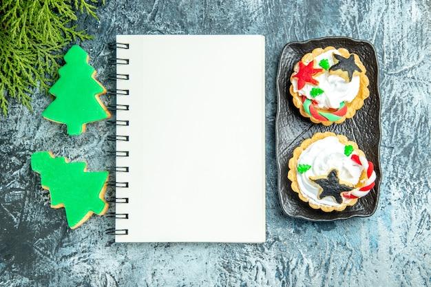 회색 테이블에 상위 뷰 노트북 작은 타르트 크리스마스 트리 비스킷 무료 사진