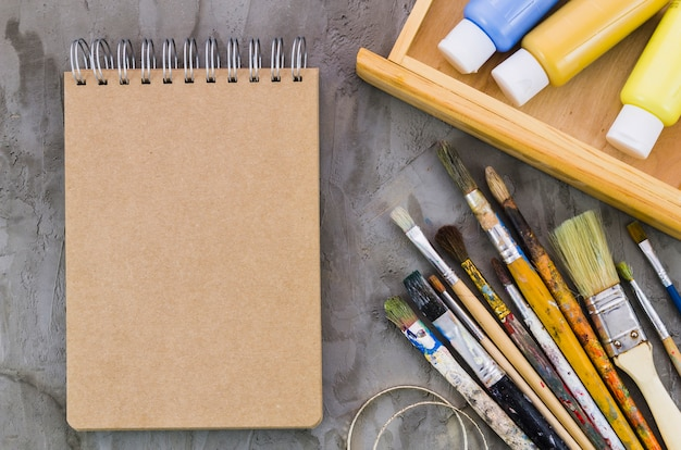 Top view notebook surrounded by painting elements Free Photo