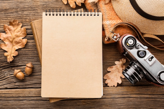 Top view of notebook with autumn leaves and hat Premium Photo