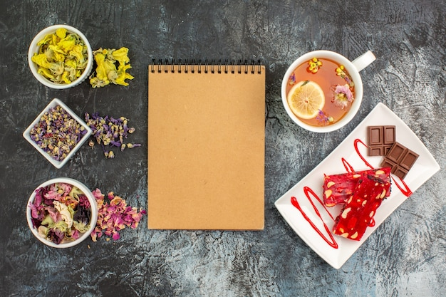 Top view of notebook with bowls of dry flowers and a cup of tea near a plate of chocolate Free Photo