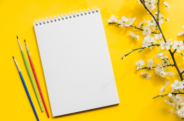 Top view notebook with branch of flowers Free Photo