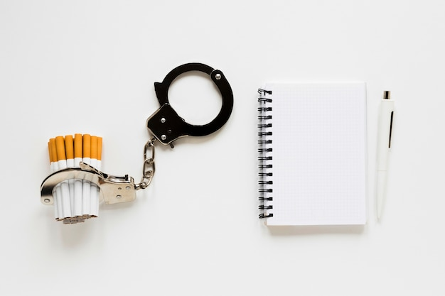 Top view notebook with cigarette and handcuffs Free Photo