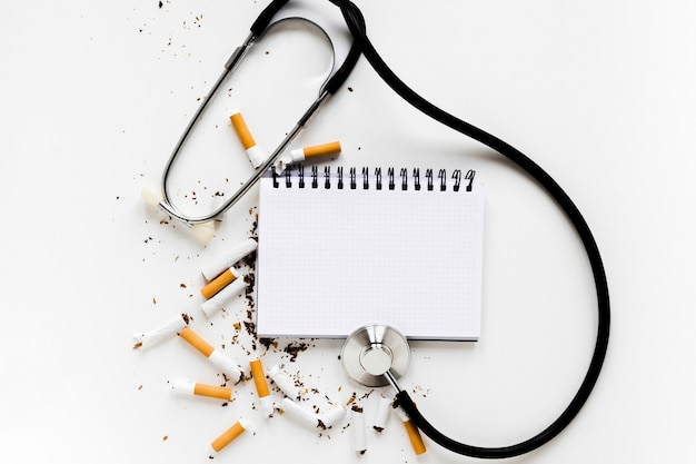Top view notebook with cigarettes and stethoscope Free Photo