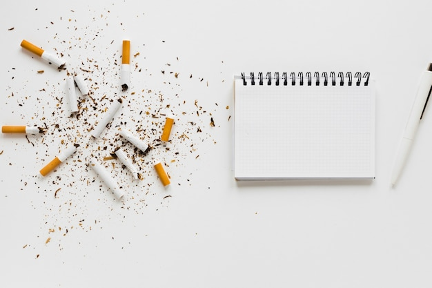 Top view notebook with cigarettes Free Photo