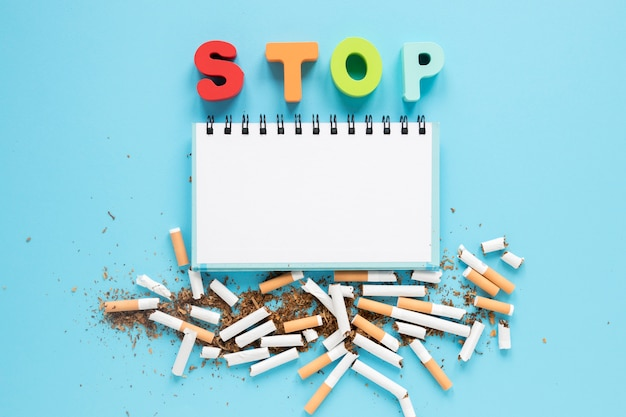 Top view notebook with colorful word and cigarettes Free Photo