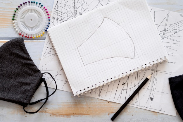 Top view of notebook with face mask design Free Photo