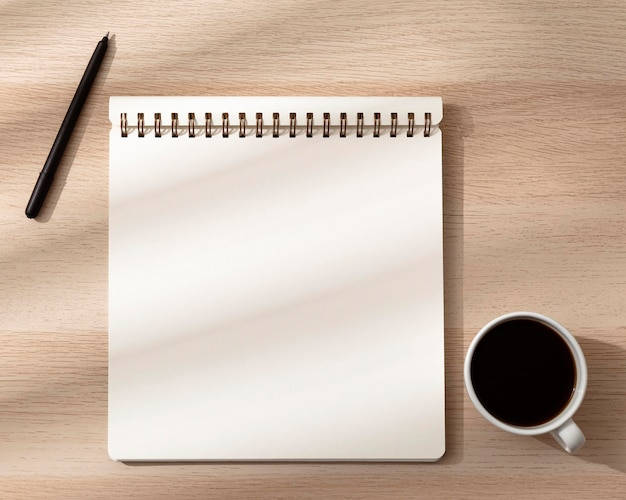 Top view of notebook with mug and pen Free Photo
