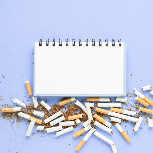 Top view notebook with pile of cigarettes Free Photo
