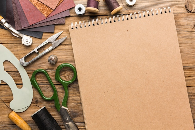 Top view of notebook with scissors and leather Free Photo