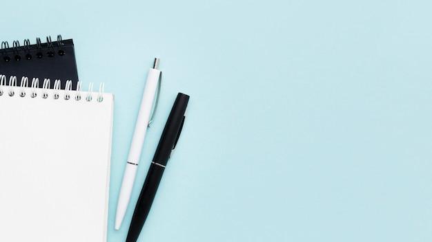 Вид сверху на блокноты и ручки Premium Фотографии