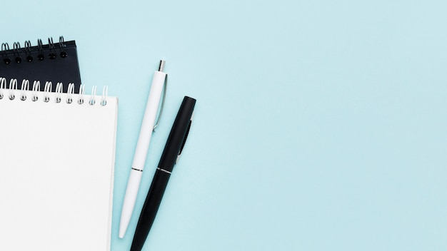 Top view notebooks and pens arrangement Free Photo