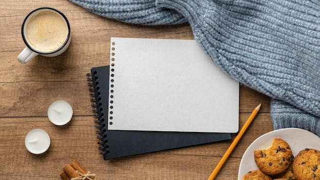 Top view of notebooks with cup of coffee and sweaters Premium Photo