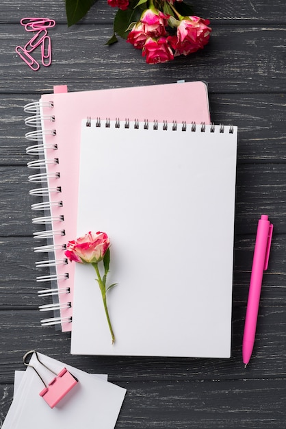 Top view of notebooks on wooden desk with bouquet of roses and pen Free Photo