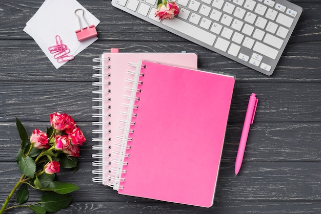 Top view of notebooks on wooden desk with bouquet of roses and sticky notes Free Photo