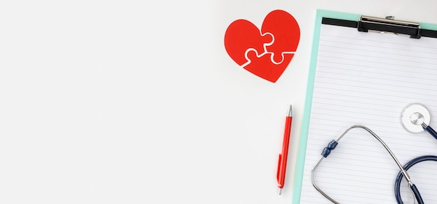 Top view of notepad with puzzle paper heart and copy space Free Photo