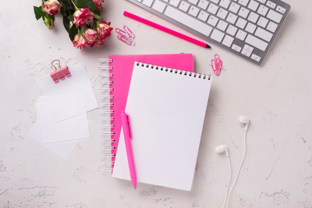 Top view of notepads on desk with bouquet of roses Free Photo