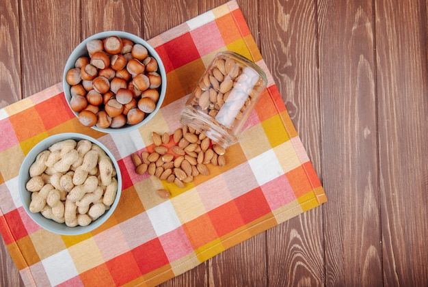 Top view of nuts peanuts hazelnuts in bowls and almond scattered from a glass jar on plaid table napkin on wooden background with copy space Free Photo