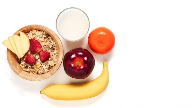 Top view of oatmeal flakes, milk, and fresh fruits on white background. copy space Premium Photo