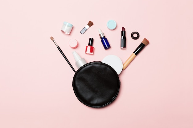 Top view od cosmetics bag with spilled out make up products on pink Premium Photo