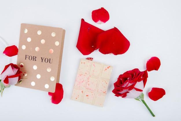 Вид сверху красная роза с маленькой открыткой и белого шоколада с лепестками красной розы на белом фоне Бесплатные Фотографии