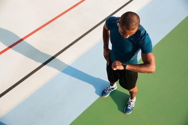 Взгляд сверху африканского спортсмена смотря его наручные часы Бесплатные Фотографии