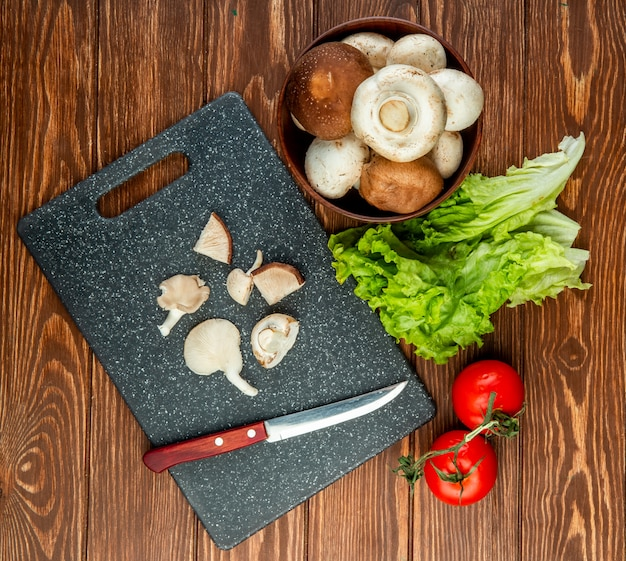 Вид сверху миску со свежими грибами и нарезанные грибы с кухонным ножом на черную доску и салат из помидоров на деревенском дереве Бесплатные Фотографии