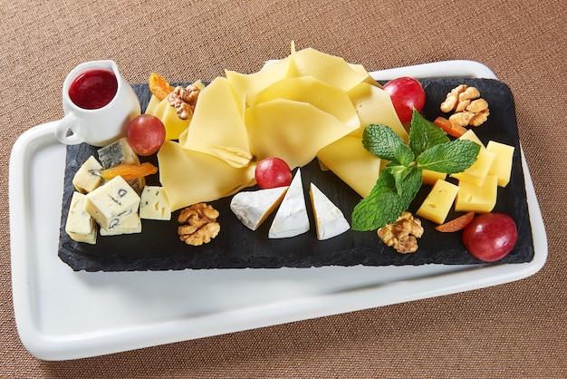 ゴーダチーズブリーブルーチーズクルミブドウとジャムの小さな瓶とチーズプレートのトップビュー 無料写真