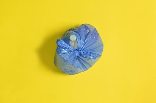 Вид сверху на закрытый синий мешок для мусора на желтом фоне Premium Фотографии