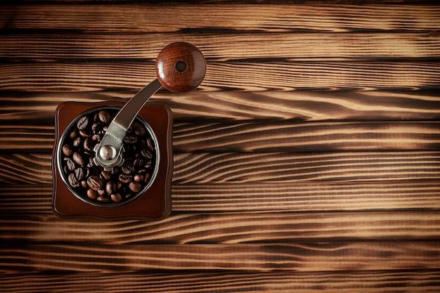 木製のテーブルにコーヒー豆とコーヒーグラインダーの上面図 Premium写真
