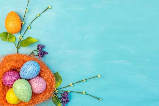Вид сверху красочные пасхальные яйца в оранжевом гнезде и весенние цветы на бирюзовом фоне с пространством сообщений Premium Фотографии