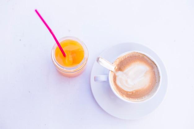 テーブルの上のコーヒーとオレンジジュースのカップの平面図です。昼間、ライフスタイル Premium写真