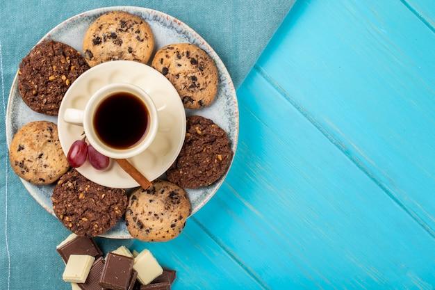 コピースペースと青色の背景にオートミールクッキーとチョコレートを添えて一杯のコーヒーのトップビュー 無料写真