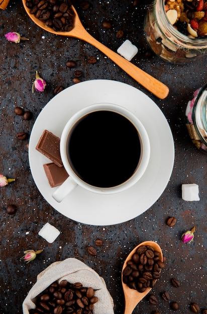 黒い背景にチョコレートとコーヒーのカップとコーヒー豆と木のスプーンのトップビュー 無料写真