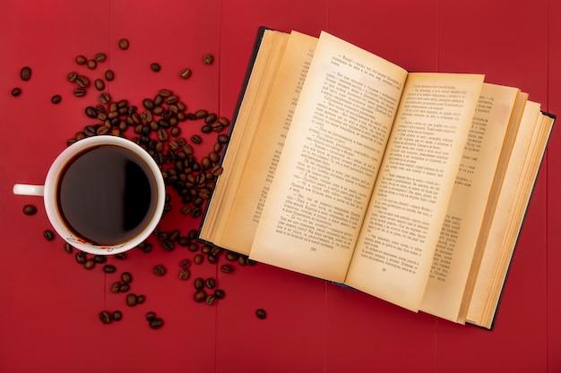 赤の背景に分離されたコーヒー豆とコーヒーのカップの上から見る 無料写真