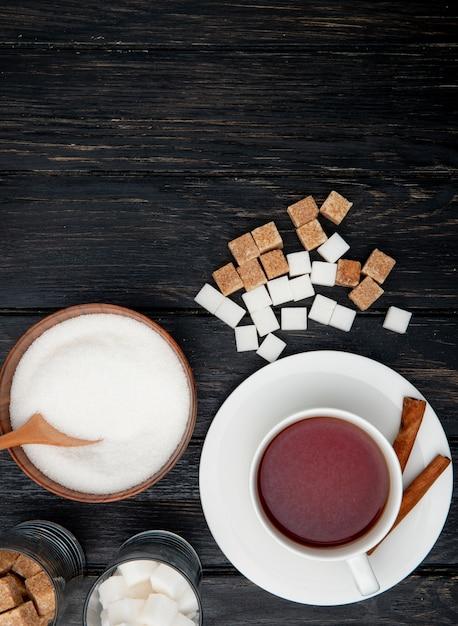 シナモンスティックと木製のボウルに白いグラニュー糖と黒の木製の背景に角砂糖とお茶のカップのトップビュー 無料写真