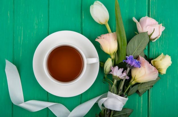 緑の木の背景にデイジーローズやチューリップのような花とお茶の上面図 無料写真